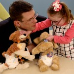 Dr. Stefan Friedrichsdorf talked quietly to Kali McKellips, 8, as she arranged her stuffed dogs for a picture.